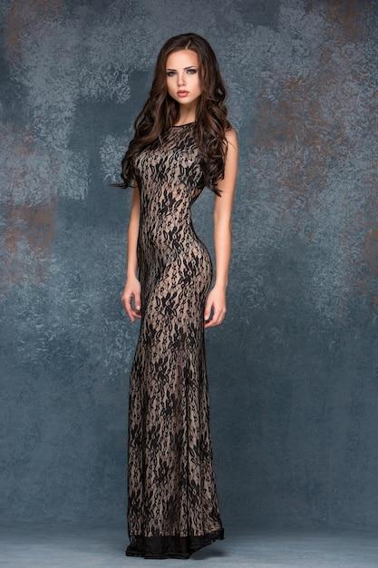 Mooie jonge brunette vrouw met haar haar poseren in ai lange jurk. Gratis Foto