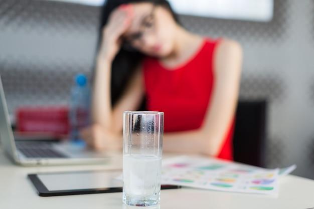 Mooie, jonge businesslady in rode jurk en bril zitten aan de tafel en werken Premium Foto