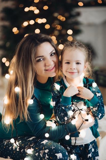 Mooie jonge dame en mooi meisje met glanzende kerstverlichting rond hun schouders. vakantie concept Premium Foto