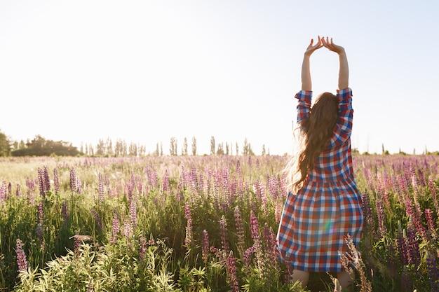 Mooie jonge dame lopen in bloem veld tijdens zonsondergang, dragen zomer lichte jurk. Gratis Foto