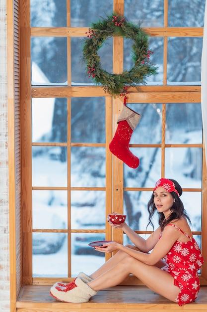 Mooie jonge donkerbruine vrouw die rode pyjama draagt die thuis door het venster zitten Gratis Foto