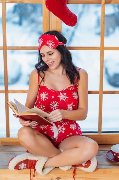 Mooie jonge donkerbruine vrouw die rode pyjama draagt en door het venster leest Gratis Foto