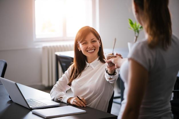 Mooie jonge donkerbruine vrouw die verfrissend roomijs in het bureau heeft Premium Foto