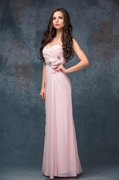 Mooie jonge donkerbruine vrouw met haar haar het stellen in ai lange roze kleding. Gratis Foto