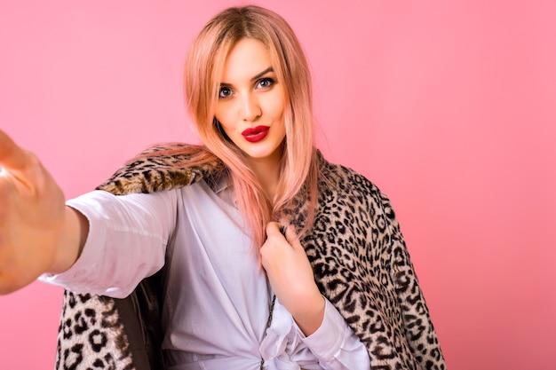 Mooie jonge elegante vrouw selfie maken op roze achtergrond, trendy kapsel en lichte make-up, kus maken en kijken op camera. Gratis Foto