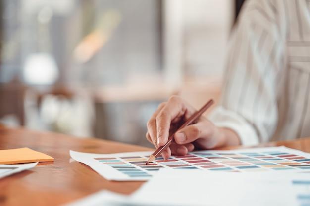 Mooie jonge freelance grafische ontwerper die kleurensteekproeven kiezen voor het ontwerpen van de mobiele lay-out van toepassingsschermen op modern kantoor. Premium Foto