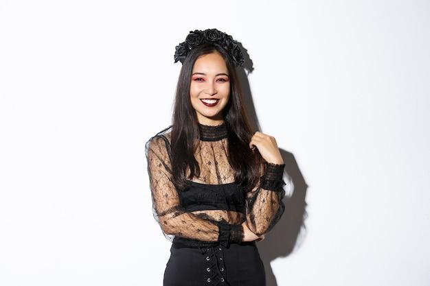 Mooie jonge gelukkige vrouw die geniet van halloween-feest, glimlachend en vrolijk kijkt terwijl ze haar boze heks kostuum draagt voor trick or treat, staande op een witte achtergrond. Gratis Foto