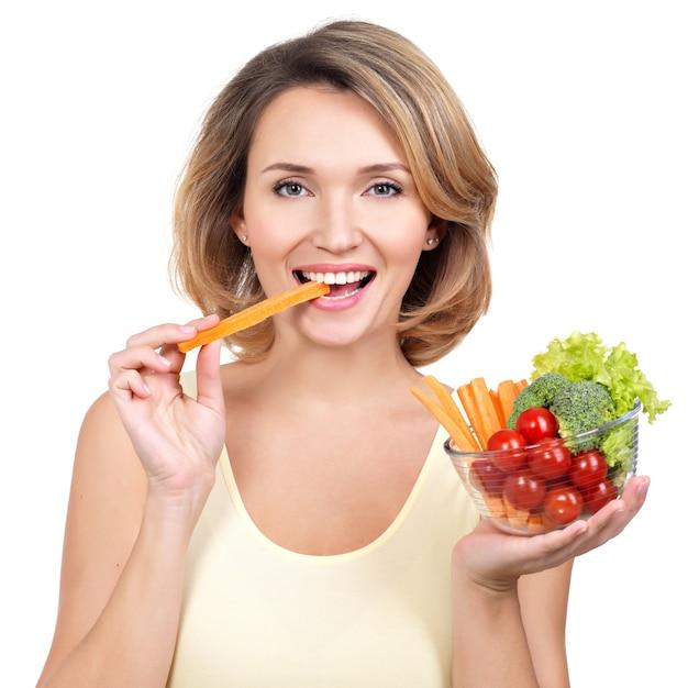 Mooie jonge gezonde vrouw die een salade eet - die op wit wordt geïsoleerd. Gratis Foto