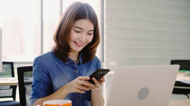 Mooie jonge glimlachende aziatische vrouw die aan laptop werkt terwijl het genieten van van het gebruiken van smartphone op kantoor. Gratis Foto