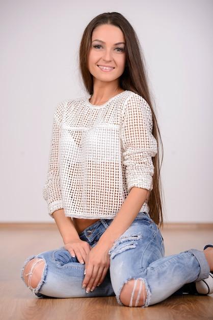 Mooie jonge lange haren vrouw zittend op de vloer. Premium Foto