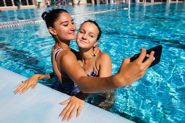 Mooie jonge meisjes die een selfie nemen bij het zwembad Gratis Foto