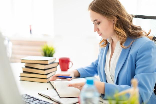 Mooie jonge meisjeszitting bij bureau in bureau, een pen in haar hand houdt en een boek leest. Premium Foto