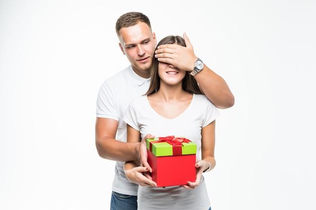 Mooie jonge paar man geeft zijn dame rode geschenkdoos verrassing geïsoleerd op wit Gratis Foto