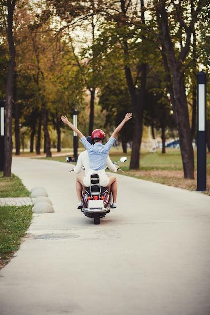 Mooie jonge paar rijden scooter Premium Foto