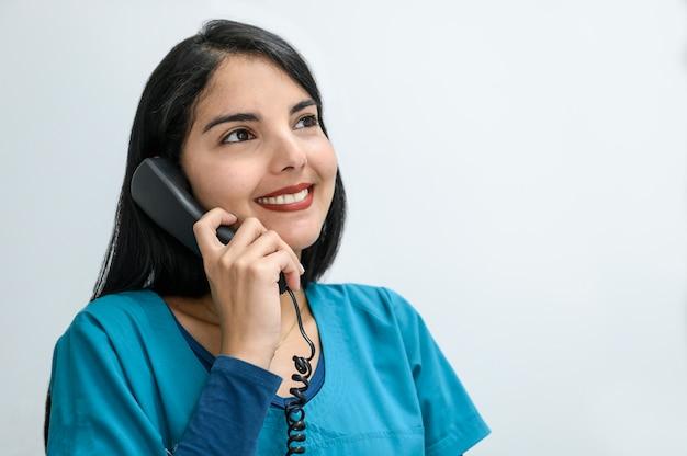 Mooie jonge receptioniste beantwoordt telefoontjes. Premium Foto