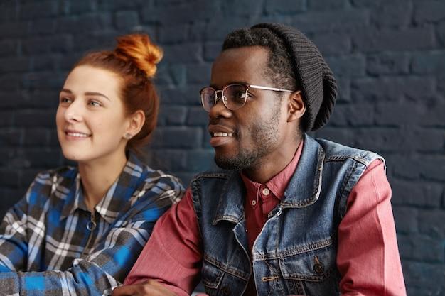 Mooie jonge roodharige blanke vrouw met haarbroodje ontspannen bij coffeeshop Gratis Foto