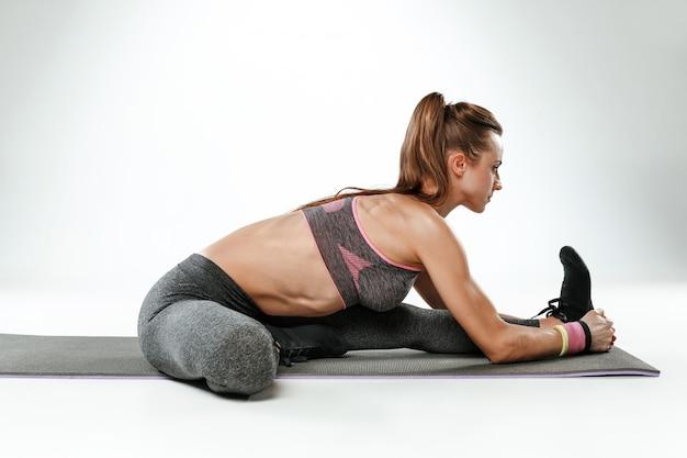 Mooie jonge slanke vrouw doet rekoefeningen in de sportschool tegen een witte achtergrond Gratis Foto