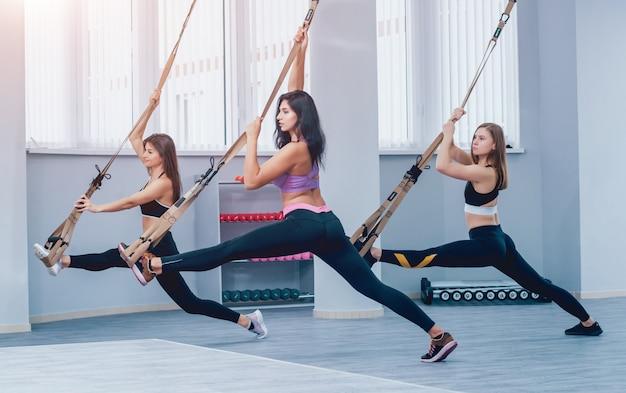 Mooie jonge sportvrouwen trainen met trx in de sportschool Premium Foto