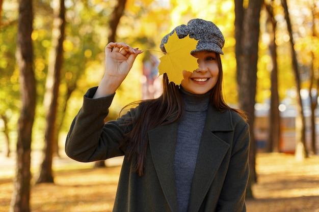 Mooie jonge stijlvolle gelukkige vrouw met een glimlach in een modieuze jas met een vintage hoed met een geel herfstblad bedekt haar gezicht in het park Premium Foto