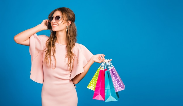 Mooie jonge stijlvolle sexy vrouw in roze luxe jurk, zomer modetrend, chique stijl, zonnebril, blauwe studio achtergrond, winkelen, papieren zakken vasthouden, praten op mobiele telefoon, shopaholic Gratis Foto