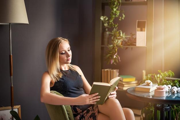 Mooie jonge succesvolle blondevrouw die een boek lezen Premium Foto