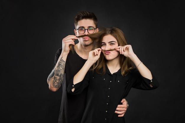 Mooie jonge verliefde paar maken nep-snor van haar terwijl je tegen de zwarte muur grappige snor. Premium Foto