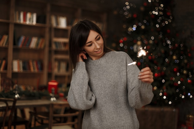 Mooie jonge vrolijke vrouw in een gebreide modieuze trui houdt een sterretje van de kerstboom in een vintage kamer. magische nieuwjaarssfeer. leuk meisje. Premium Foto