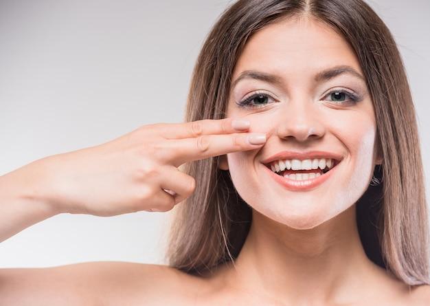 Mooie jonge vrouw aan te raken van de huid of room toe te passen. Premium Foto