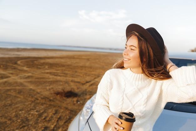 Mooie jonge vrouw buiten op het strand tijdens zonsondergang, zittend op een auto, koffie drinken Premium Foto