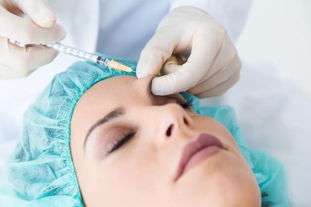 Mooie jonge vrouw die botox kosmetische injectie in haar gezicht krijgt. Gratis Foto