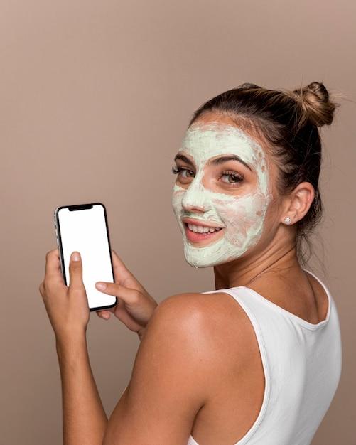 Mooie jonge vrouw die cosmetische producten probeert Gratis Foto