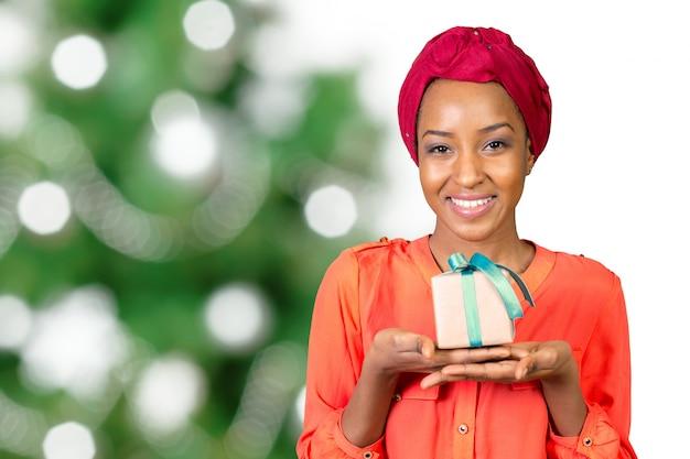 Mooie jonge vrouw die een geschenk houdt Premium Foto