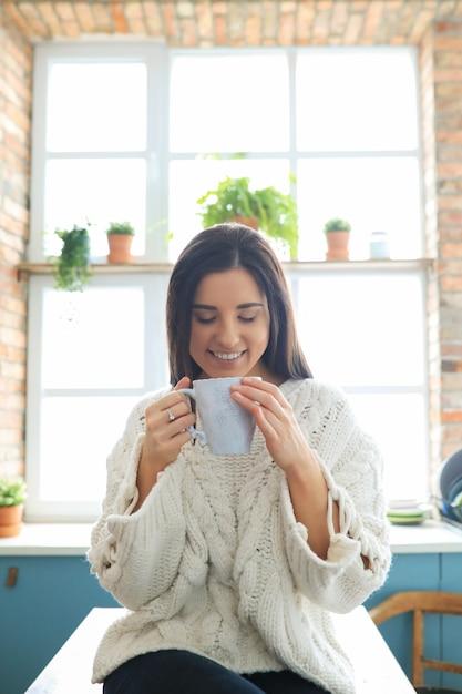 Mooie jonge vrouw die een warme drank in de keuken drinkt Gratis Foto