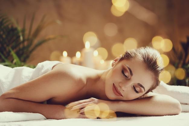Mooie jonge vrouw die en op haar massage ligt te wachten. spa concept Gratis Foto
