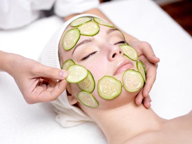 Mooie jonge vrouw die gezichtsmasker van komkommer in schoonheidssalon ontvangt Gratis Foto