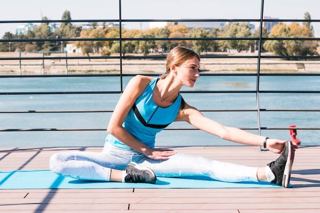 Mooie jonge vrouw die haar been ay in openlucht uitrekt Gratis Foto
