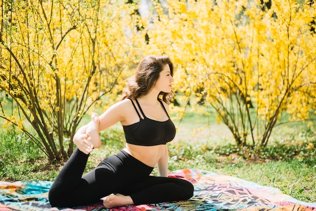 Mooie jonge vrouw die haar been in tuin uitrekt Gratis Foto