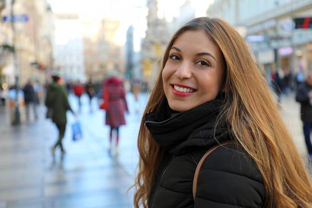 Mooie jonge vrouw die in de hoofdstraat van wenen bij winterseizoen, oostenrijk loopt Premium Foto