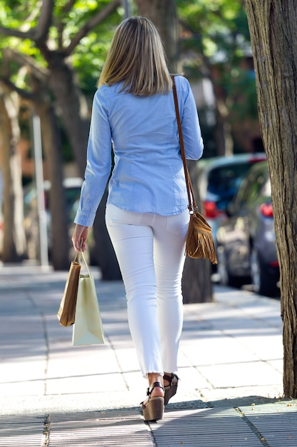 Mooie jonge vrouw die in de straat loopt. winkelconcept. Gratis Foto