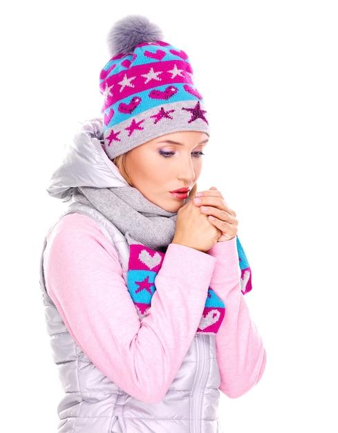 Mooie jonge vrouw die in de winterkleren haar handen verwarmt Gratis Foto