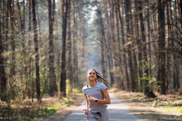 Mooie jonge vrouw die in groen park op zonnige de zomerdag loopt Gratis Foto