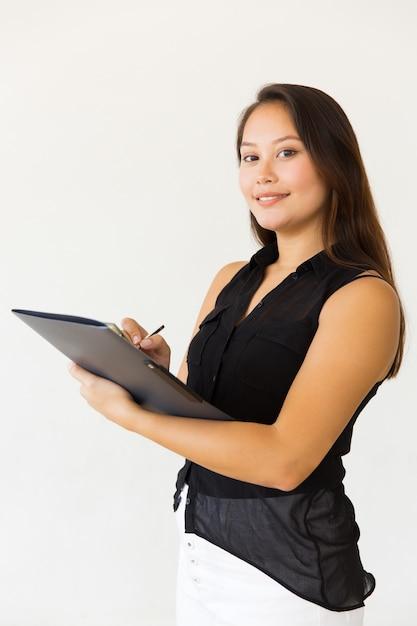 Mooie jonge vrouw die in omslag schrijft Gratis Foto