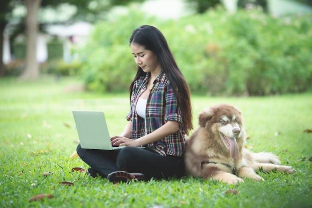 Mooie jonge vrouw die laptop met haar kleine hond in een park in openlucht met behulp van. levensstijl portret. Gratis Foto