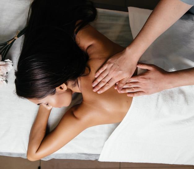 Mooie jonge vrouw die massage met stenen in kuuroordsalon heeft. Premium Foto
