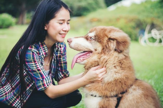 Mooie jonge vrouw die met haar kleine hond in een park in openlucht speelt. levensstijl portret. Gratis Foto
