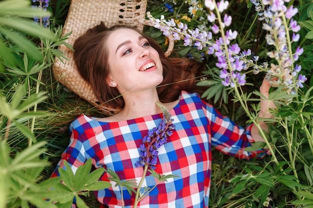 Mooie jonge vrouw die op het gebied in groen gras en bloemen ligt. Gratis Foto