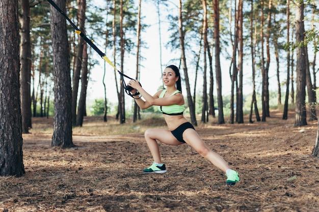 Mooie jonge vrouw die trxoefening met de slinger van de opschortingstrainer in gezonde openlucht doet Premium Foto