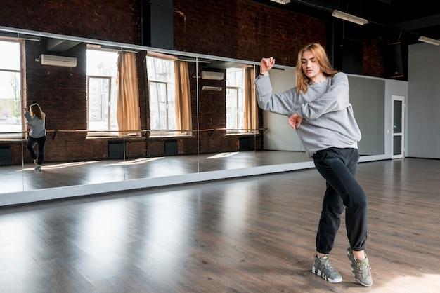 Mooie jonge vrouw die voor spiegel danst Gratis Foto