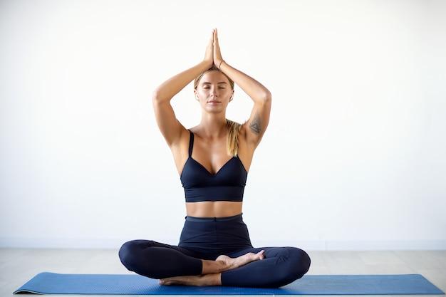 Mooie jonge vrouw die yoga doet Premium Foto