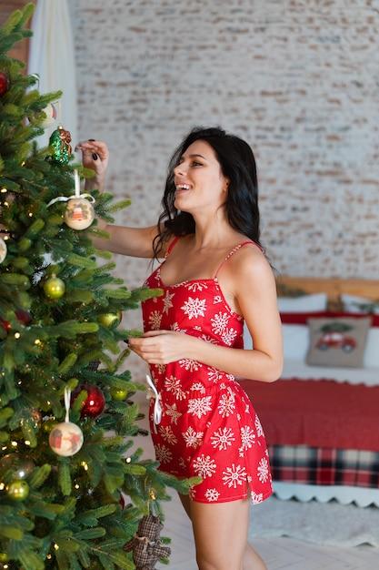 Mooie jonge vrouw die zich door de boom bevindt Gratis Foto